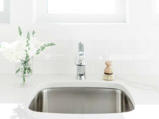 stainless steel sink against white walls with natural scrub brush
