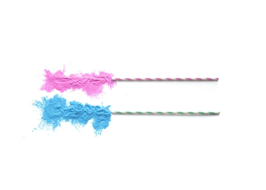candy sticks with pink and blue sugar against white background
