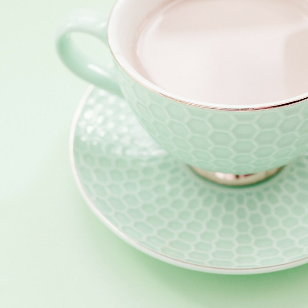 pale green china tea cup on green background