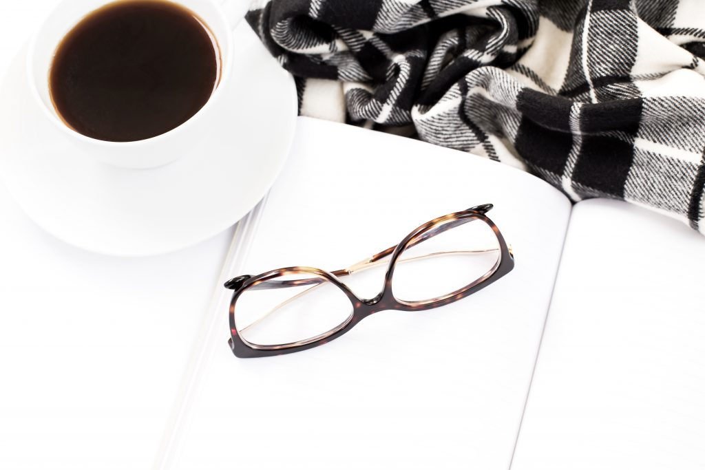 white coffee mug filled with black coffee on white desk with black glass frames and black and white plaid scarf