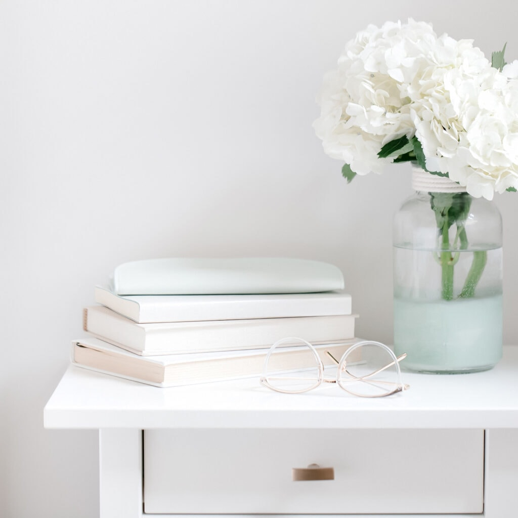 white fresh flowers in vase on bedside table against white wall