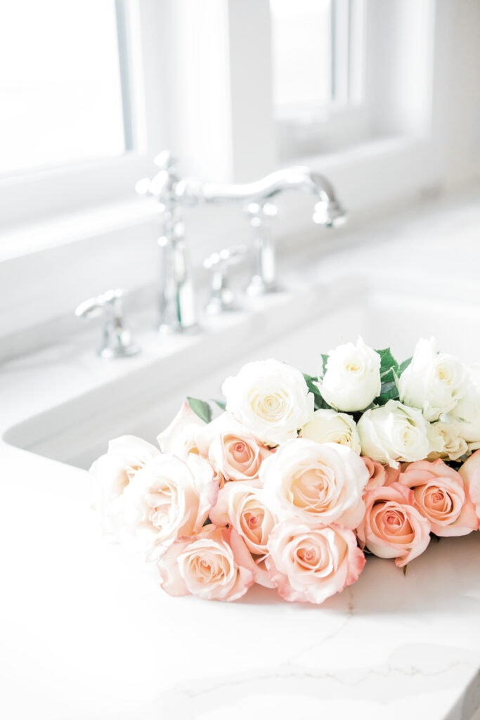 fresh cut white and pink roses in white kitchen sink