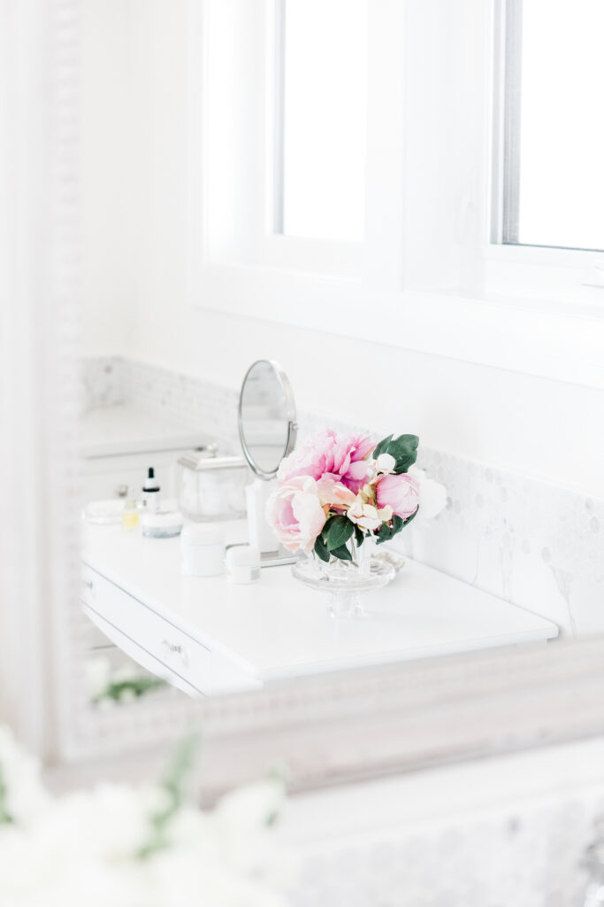 pink flowers in vase in white bathroom