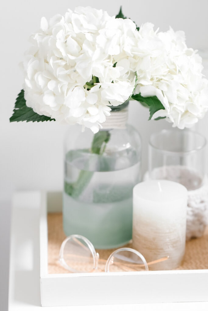 white hydrangeas in glass vase on bedside table