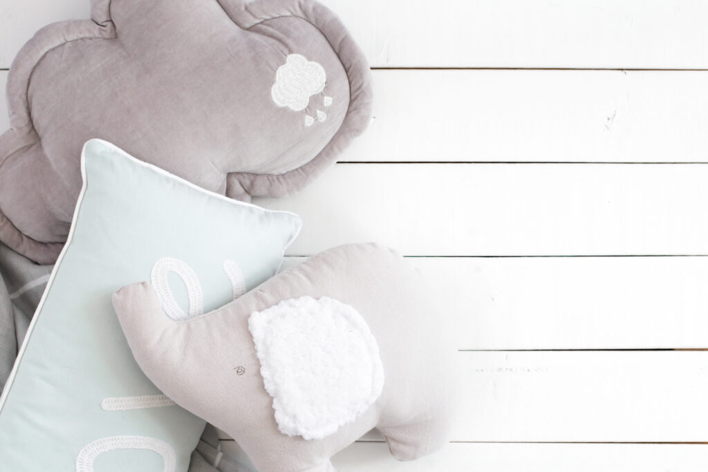 grey elephant stuffed animal for baby against white background