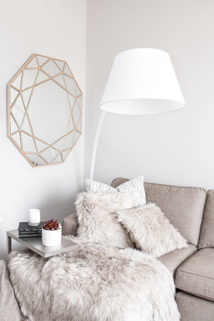 grey couch with throw pillows and fuzzy grey blanket