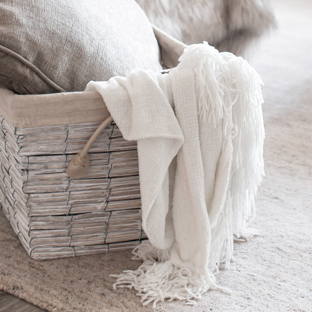 white throw blanket in grey basket with grey pillow