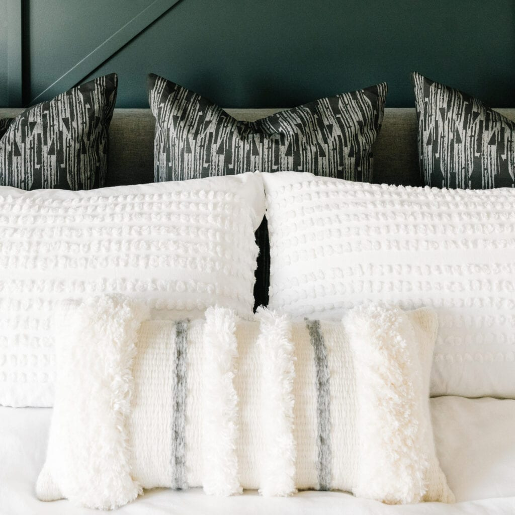 white throw pillows on a bed and white comforter