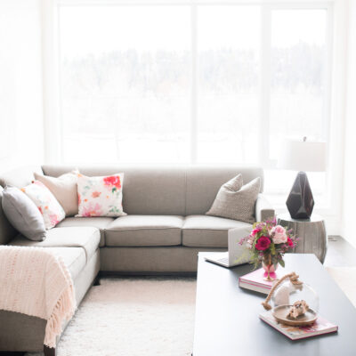 upholstered grey sofa against large windows with natural light