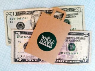 Whole Foods bag lying on top of money