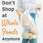 woman holding mesh grocery bag full of produce and bread