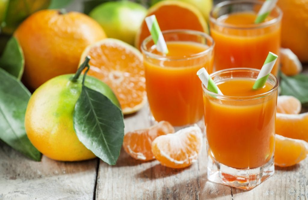 Fresh juice of ripe mandarins in a small glass with striped straw