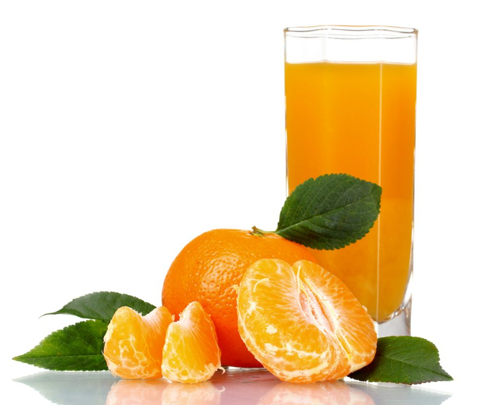 glass of tangerine juice against white background with fresh tangerines peeled