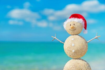 snowman made of sand with red Santa hat on against turquoise blue beach water and clouds in sky