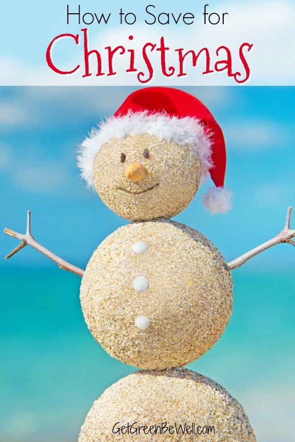 sandcastle snowman with red Santa hat on beach
