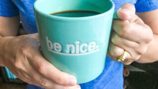 woman holding blue coffee cup with words be nice