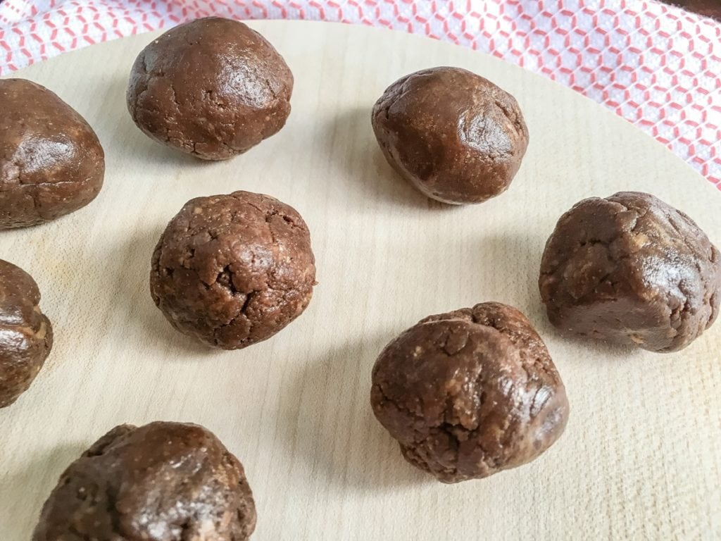 chocolate no bake protein balls with protein powder on wooden serving tray