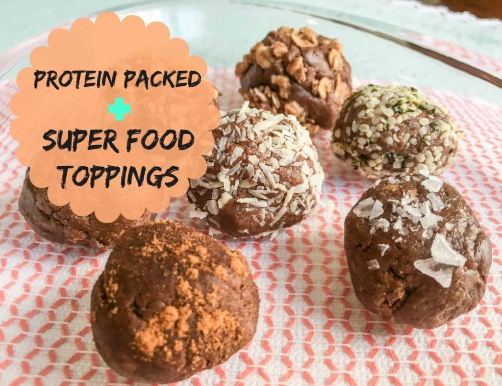 chocolate no bake protein balls with protein powder rolled in superfood toppings on glass serving tray