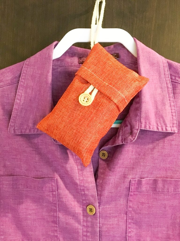 orange linen bag with wood button hanging on closet hanger with purple shirt