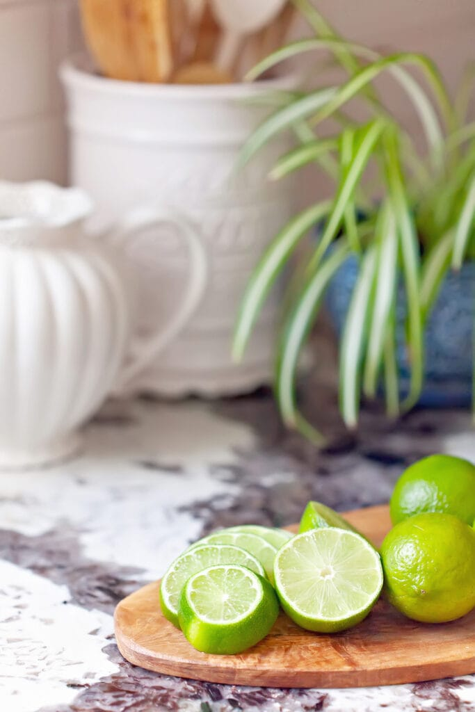 limes on wooden cutting board on kitchen counter