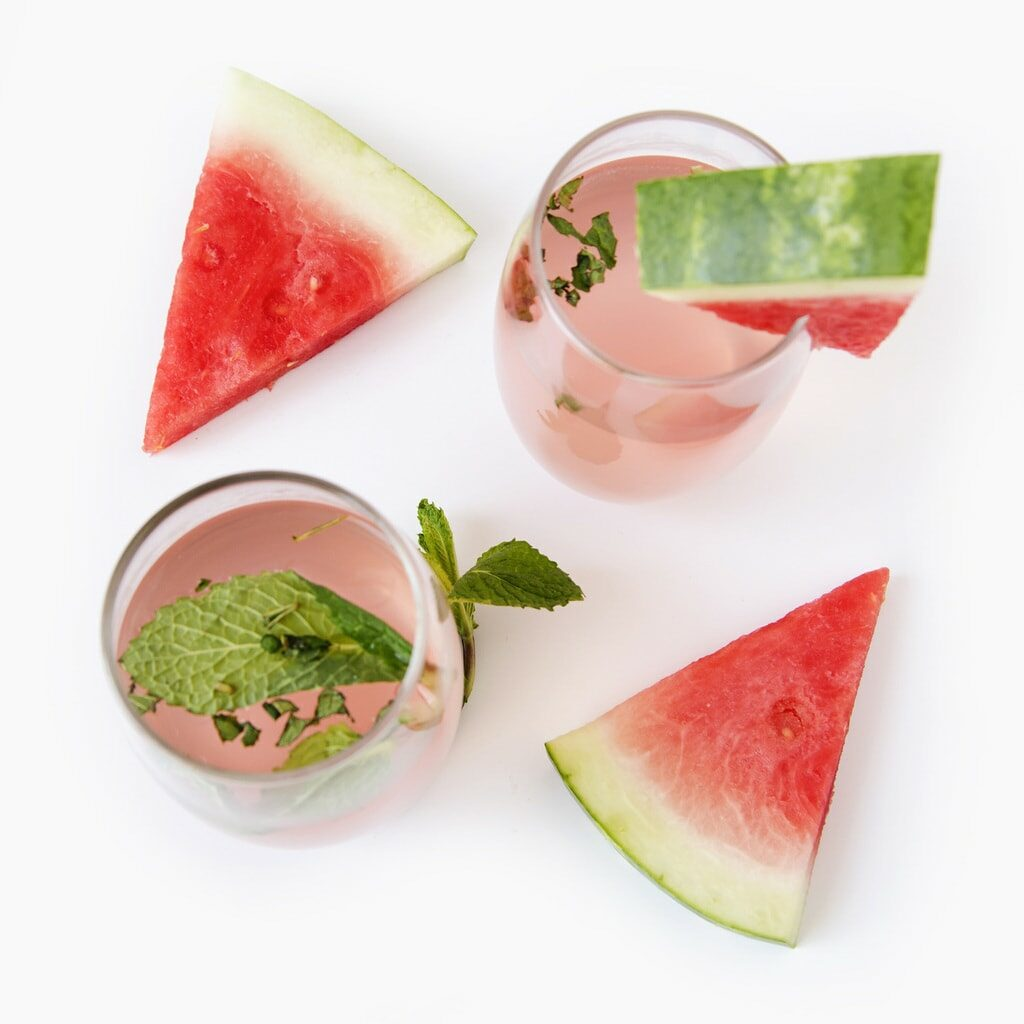 watermelon wedges in pink drinks against white background