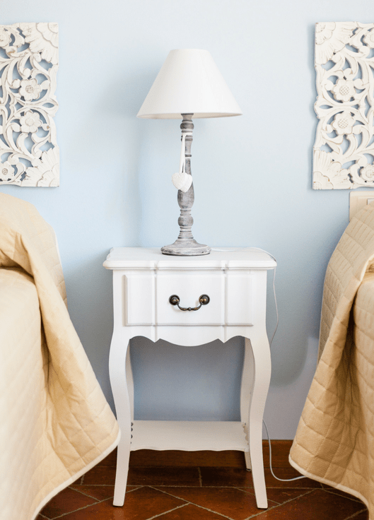 white wooden nightstand with silver lamp on top between two twin beds with linen comforters
