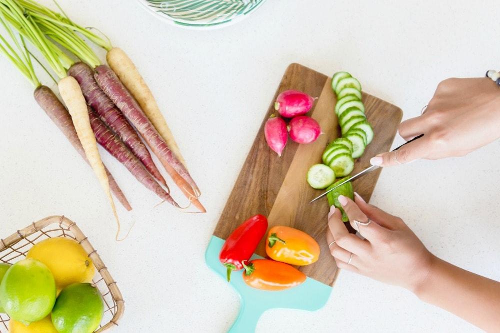 woman cutting vegetables on wood cutting board