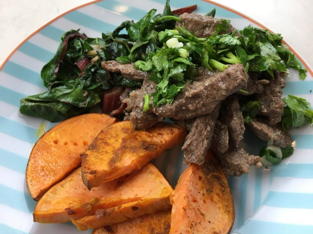 sweet potatoes kale and meat with chimichurri sauce on a plate