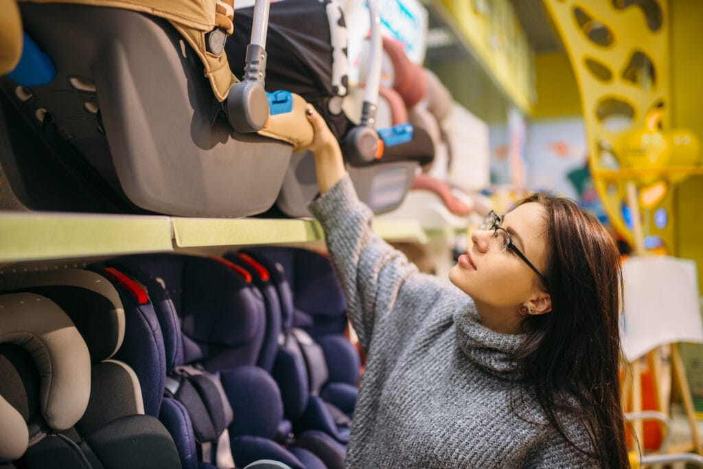 Pregnant woman choosing child car seat in store.