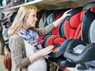 woman choosing child car seat for newborn baby in shop