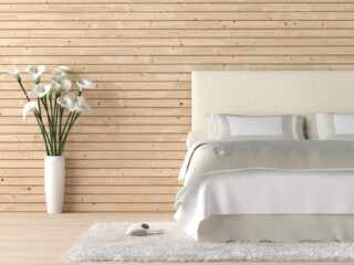 minimalist bedroom with white sheets against a wooden slat wall with a flower vase on the floor