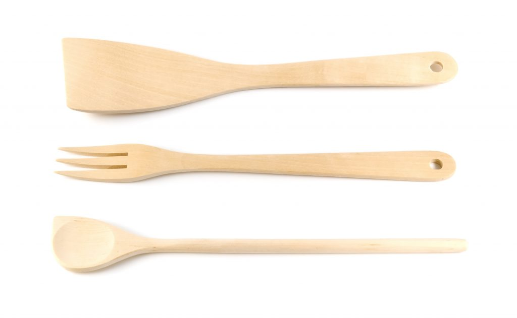 Wooden spoon, spatula, fork on a white background.