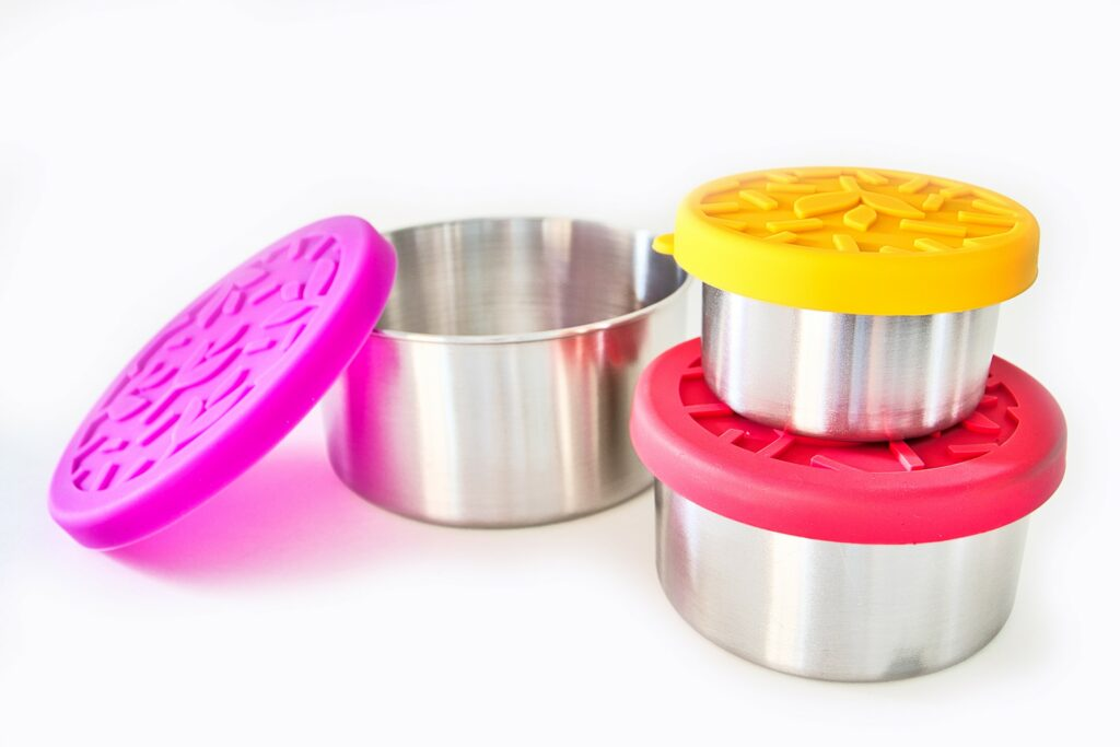 three stainless steel bowls with brightly colored silicone lids