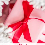 Christmas present wrapped in pink paper with red bow against white tree branches healthy stocking stuffer ideas