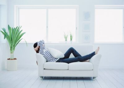 woman relaxing on white couch in white room with lots of windows and minimalistic decor