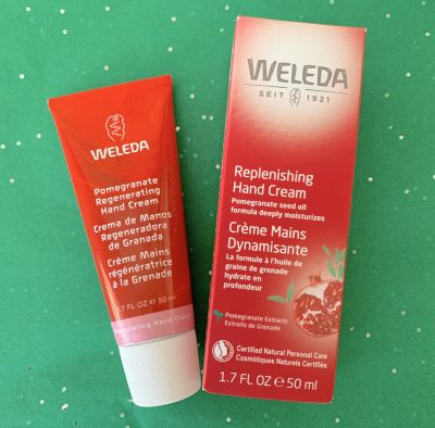 red bottle Pomegranate Replenishing Hand Cream Weleda against green background