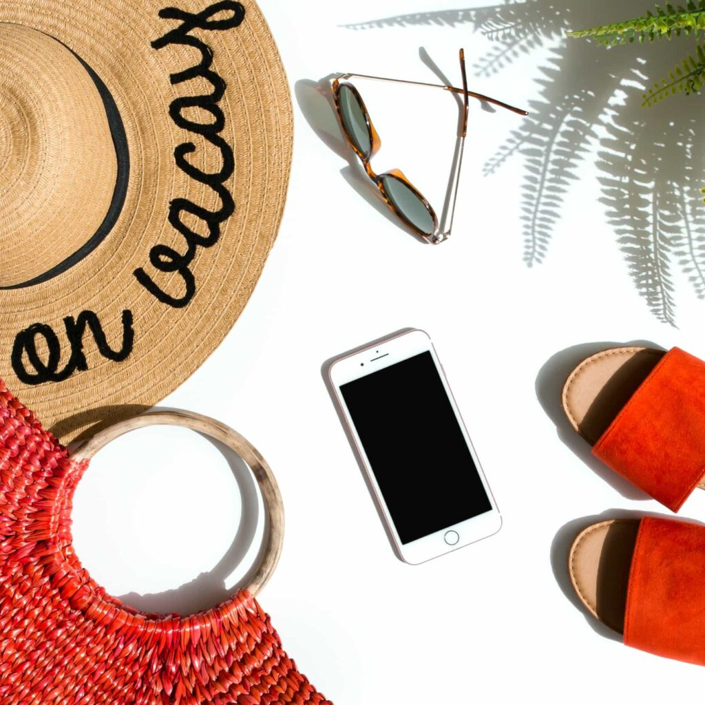 vacation hat on white background with bag phone sunglasses and orange shoes