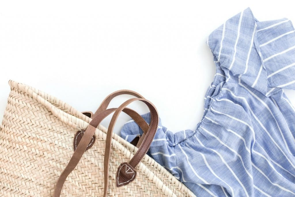 straw bag and denim shirt on white background