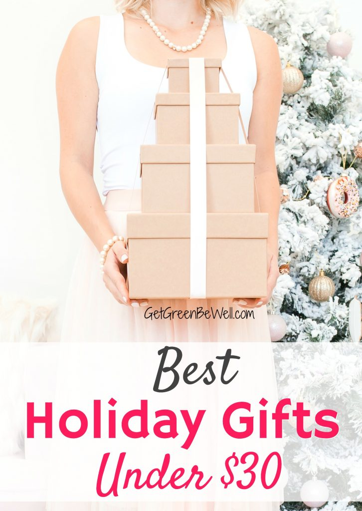 Woman holding stack of presents wrapped in brown paper and white bow holiday gift guide