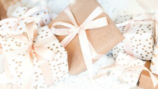 holiday gifts wrapped in brown and white paper with gold polka dots and pink bows holiday gift guide