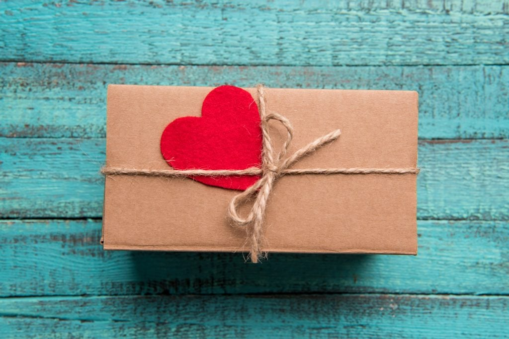 gift wrapped in brown paper with twine bow and red felt heart against blue wooden slat backdrop