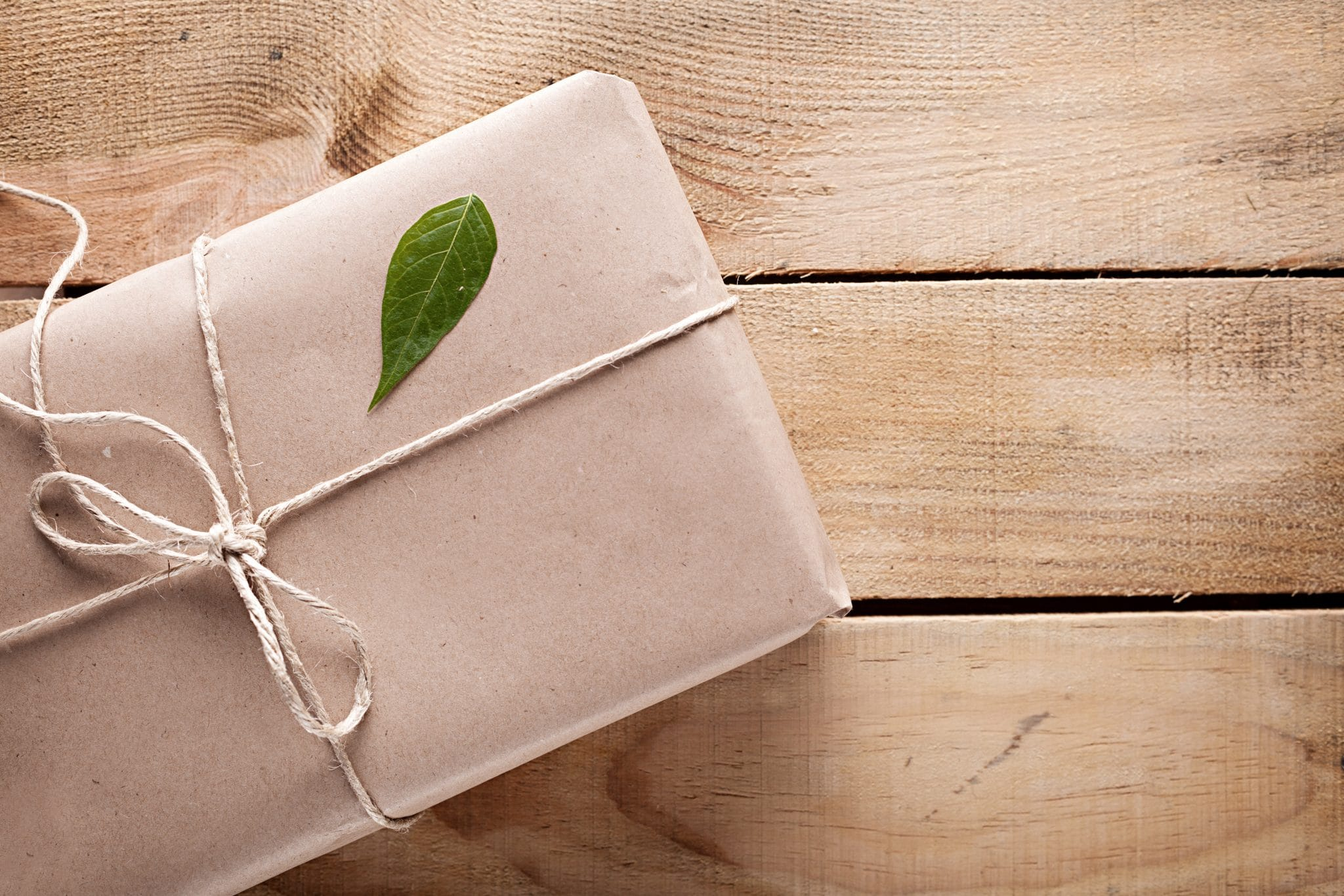 Gift Box With A Green Leaf On It Wooden Background