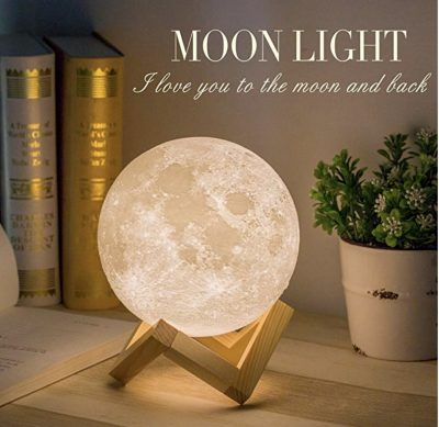 circular lamp that looks like the moon lit up on wooden base on bookshelf holiday gift guide