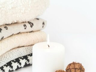 cozy winter sweaters stacked up next to white candle with flame and two pinecones