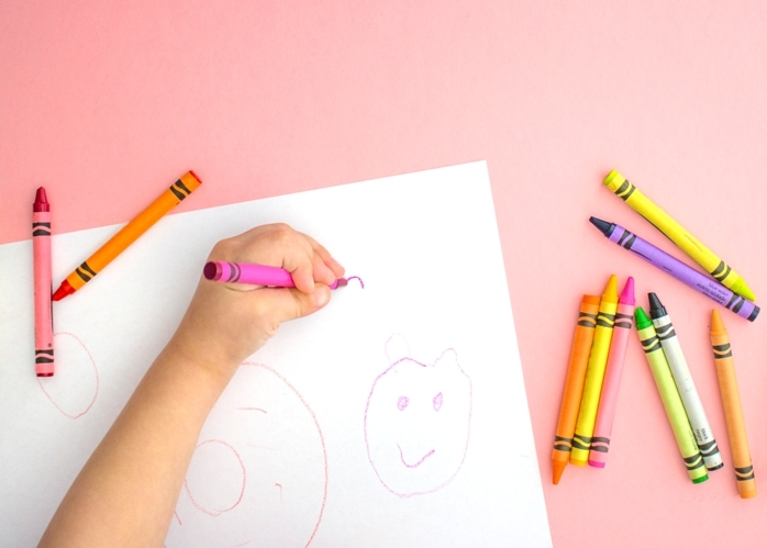 Kids hand coloring with crayons