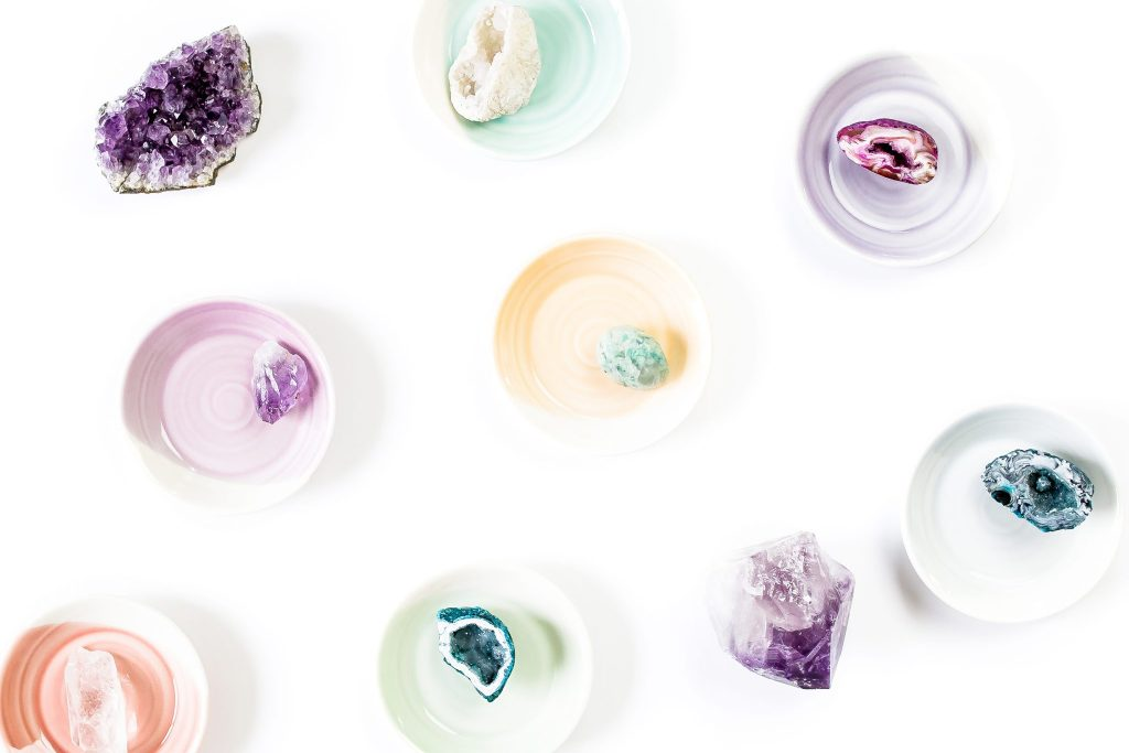 white background with pastel bowls filled with crystals