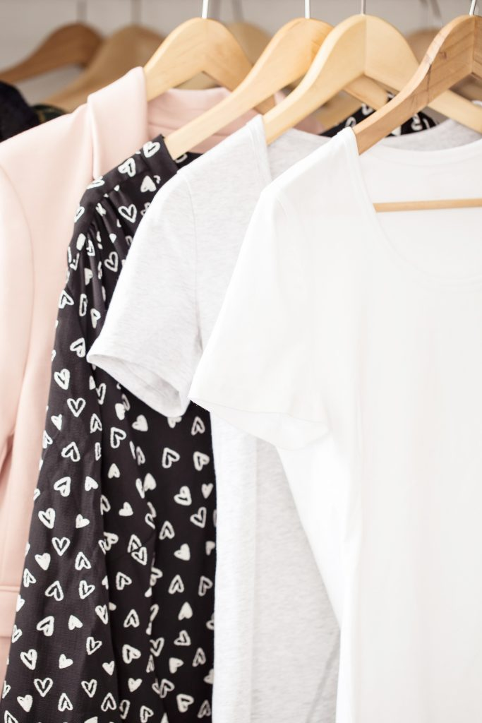 white black and pink women's clothing hangin on wooden hangers in closet