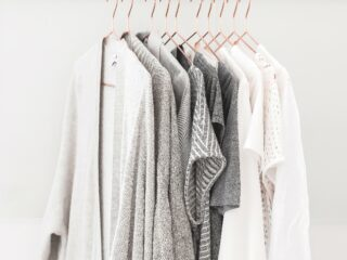 womens clothes in shades of white and grey hanging on copper hangers on curtain rod