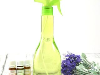 Green Spray Bottle with essential oils and lavender flowers on wooden table