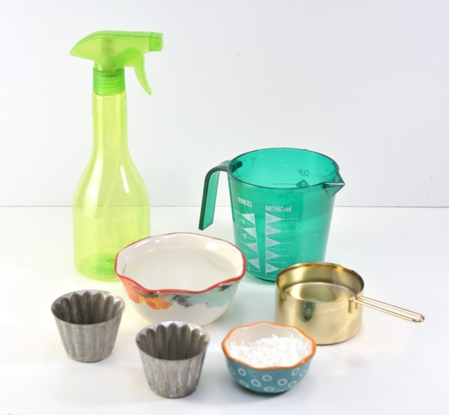 green spray bottle blue measuring cup measuring dishes on white countertop